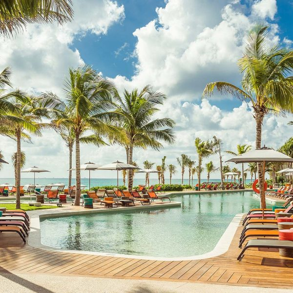resort pool with cabana seating by the beach